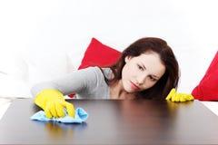 Schöne junge Frau, die zu Hause aufräumt. Lizenzfreies Stockbild