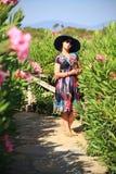 Schöne junge Frau in einem Hut draußen Stockbild
