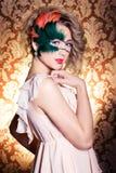Schöne junge Frau in einer grünen mysteriösen venetianischen Maske ein Karneval des neuen Jahres, Weihnachtsmaskerade, ein Tanzcl Stockfotografie