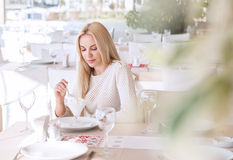 Schöne junge Frau im Café am sonnigen Tag Lizenzfreie Stockfotografie