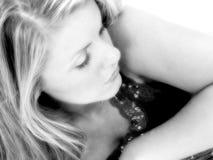 Schöne junge Frau mit dem blonden Haar, das unten schaut Stockbild