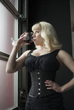 Schöne junge Frau mit dem blonden Haar ein Glas Wein trinkend Lizenzfreie Stockfotografie