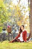 Schöne junge Frau mit dem Fahrrad, das im Park sitzt Lizenzfreie Stockfotos