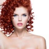 Schöne junge Frau mit dem roten gelockten Haar Stockfotos