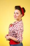 Schöne junge Frau mit der Stift-oben Verfassung und Frisur, die über rosafarbenem Hintergrund aufwerfen Stockfoto
