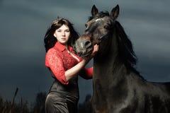 Schöne junge Frau mit einem schwarzen Pferd Lizenzfreie Stockbilder