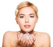 Schöne junge Frau mit Eis in ihren Händen Stockbild