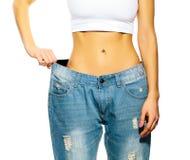 Schöne junge Frau mit großen Jeans Stockbilder
