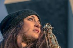Schöne junge Frau mit ihrem Saxophon Lizenzfreies Stockfoto