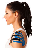 Schöne junge Frau mit kinesiotape auf ihrer Schulter zum mobili Lizenzfreie Stockfotos