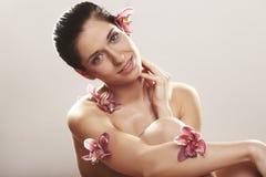 Schöne junge Frau mit Orchideeblumen Lizenzfreie Stockbilder