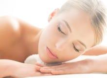 Schöne junge Frau, welche die Freizeit liegt in einer Matte im Badekurort hat Stockbilder