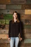 Schöne junge Geschäftsfrau, die gegen eine hölzerne Wand steht Lizenzfreies Stockbild