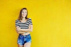 Schöne junge glückliche Frau mit den Händen faltete Aufstellung die im Freien Stockfotos