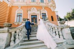 Schöne junge Hochzeitspaare, die auf Treppe des romantischen antiken Palastes gehen Lizenzfreie Stockfotos