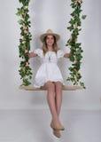 Schöne junge langbeinige Blondine in einem wenigen weißen Kleid und weißen in einem Cowboyhut auf einem Schwingen, hölzernes Schw Stockfoto