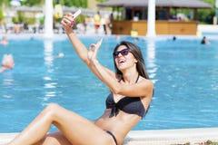Schöne junge lächelnde Frau, die den Spaß macht selfie hat Stockbilder