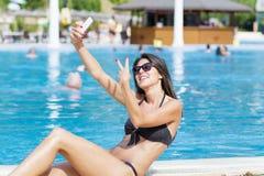 Schöne junge lächelnde Frau, die den Spaß macht selfie hat Lizenzfreie Stockfotografie