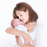 Schöne junge Mutter, die ihr neugeborenes Baby hält Stockbild