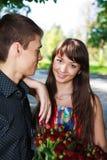 Schöne junge Paare des Porträts mit einem Blumenstrauß der roten Rosen Lizenzfreie Stockfotografie