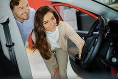 Schöne junge Paare, die einen Neuwagen dem Verkaufsstelleausstellungsraum betrachten Stockfotografie