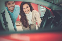 Schöne junge Paare, die einen Neuwagen dem Verkaufsstelleausstellungsraum betrachten Lizenzfreie Stockfotos