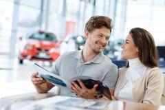 Schöne junge Paare, die einen Neuwagen dem Verkaufsstelleausstellungsraum betrachten Stockfoto