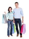 Schöne junge Paare mit Einkaufenbeuteln Lizenzfreie Stockfotografie