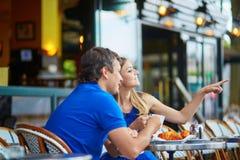 Schöne junge Paare von Touristen im Pariser Straßencafé Stockfotografie