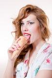 Schöne junge Pinupfrau, welche die Eistüte in camera schaut lokalisiert auf weißem copyspace Hintergrund-Porträtbild isst Stockbild