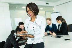 Schöne, junge, schwarze Geschäftsfrau, die eine Tablette betrachtet Stockfotos