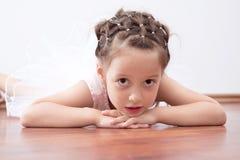 Schöne kleine Ballerina, die auf den Fußboden legt Lizenzfreies Stockfoto