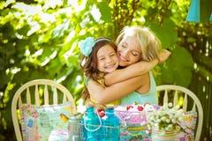 Schöne kleine Tochter umarmt Mutter im Garten im Sommer Stockfoto