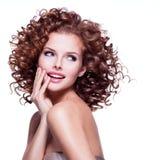 Schöne lächelnde durchdachte Frau mit dem gelockten Haar Stockfoto