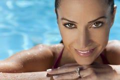 Schöne lächelnde Frau, die im Swimmingpool sich entspannt Stockbilder