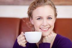 Schöne lächelnde Frau, die Tasse Kaffee genießt Stockfotos