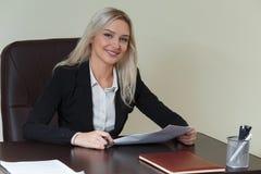 Schöne lächelnde Geschäftsfrau, die an ihrem Schreibtisch mit Dokumenten arbeitet Stockbilder