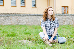Recht lächelnde glückliche Jugendliche, die draußen sitzt Stockbilder