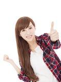 Schöne lächelnde junge Frau, die mit dem Daumen oben steht Lizenzfreie Stockbilder