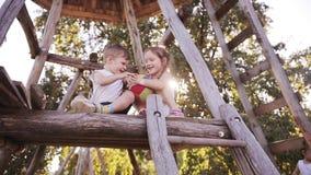 Schöne lächelnde Mädchen- und Jungengeschwister, die mit dem Ball im Freien auf Baumhaus zusammen mit ihrem Elternteil am sonnige stock footage