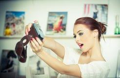 Schöne, lächelnde rote Haarfrau, die Fotos von mit einer Kamera macht Moderne attraktive Frau, die ein Selbstporträt nimmt Stockfoto
