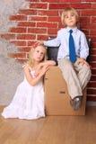 Schöne müde Kinder, die auf Koffern sitzen Lizenzfreie Stockfotos