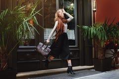 Schöne moderne junge Frau, die mit Tasche läuft Junge Frau der Schönheit auf städtischem Hintergrund Weibliche Mode Volles Kaross Lizenzfreie Stockbilder