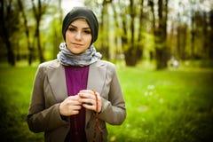 Schöne moslemische Frau tragendes hijab, das auf Rosenbeet/tespih betet Stockbild