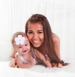 Schöne Mutter und nettes Babylächeln Stockfoto