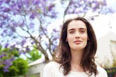 Schöne nachdenkliche Frau, die im Vorgarten steht Lizenzfreie Stockbilder