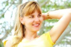 Schöne Nahaufnahme der jungen Frau in der orange Strickjacke, gegen Grün Stockfotografie