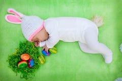 Schöne Ostern-Karte eines Babys in einer Häschenausstattung Stockfotografie