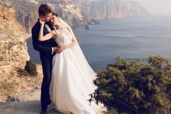 Schöne Paare herrliche Braut im Hochzeitskleid, das mit elegantem Bräutigam auf Seekosten aufwirft Stockbild