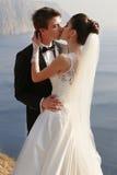 Schöne Paare herrliche Braut im Hochzeitskleid, das mit elegantem Bräutigam auf Seekosten aufwirft Stockbilder